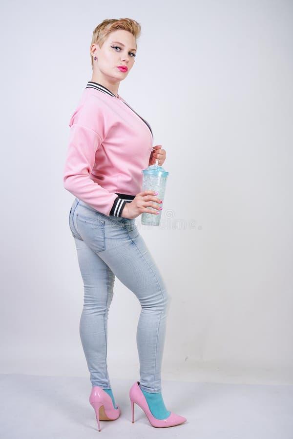 Dosyć plus wielkościowa krótkiego włosy kobieta z błękitną filiżanką woda blondynki dorosła dziewczyna jest ubranym sport różową  obrazy stock