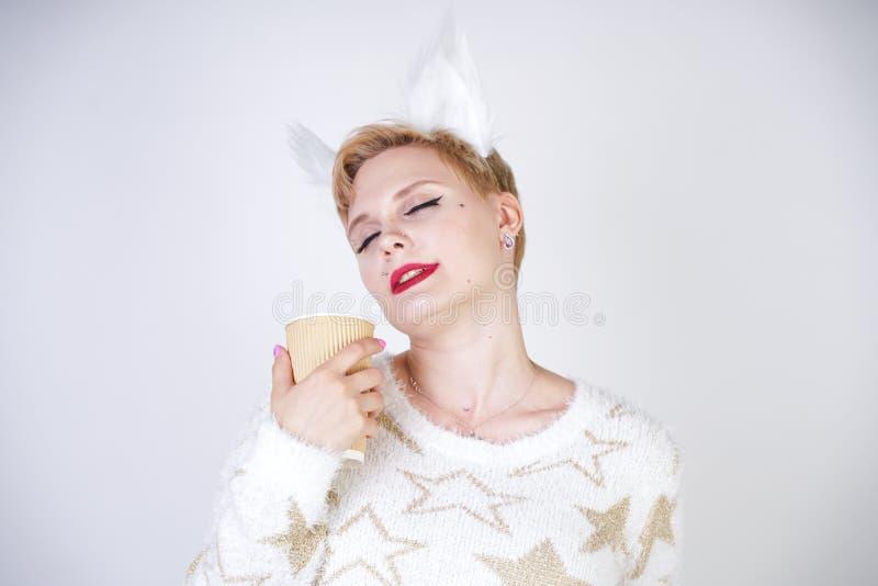 Dosyć plus wielkościowy caucasian kobiety wearng dział kotów ucho i pozować na białym pracownianym tle samotnie moda puloweru i f obrazy royalty free