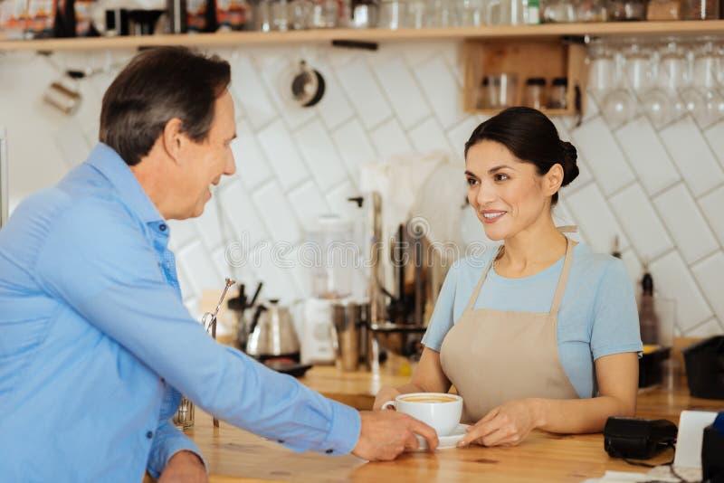 Dosyć przyjemny kelner ono uśmiecha się i komunikuje z mężczyzna zdjęcie royalty free