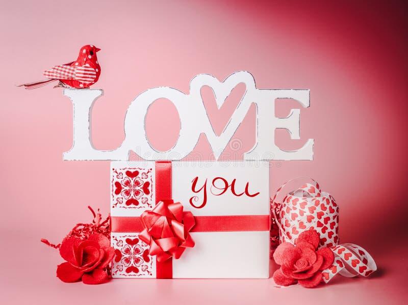 Dosyć romantyczny skład dla walentynka dnia Kocha ciebie wiadomość z prezenta pudełkiem, czerwonymi faborkami i dekoracją, Świąte zdjęcia stock