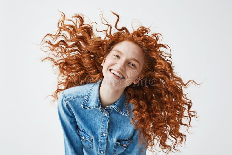 Dosyć rozochocona rudzielec dziewczyna uśmiecha się śmiać się z latać kędzierzawego włosy patrzejący kamerę nad białym tłem zdjęcia royalty free