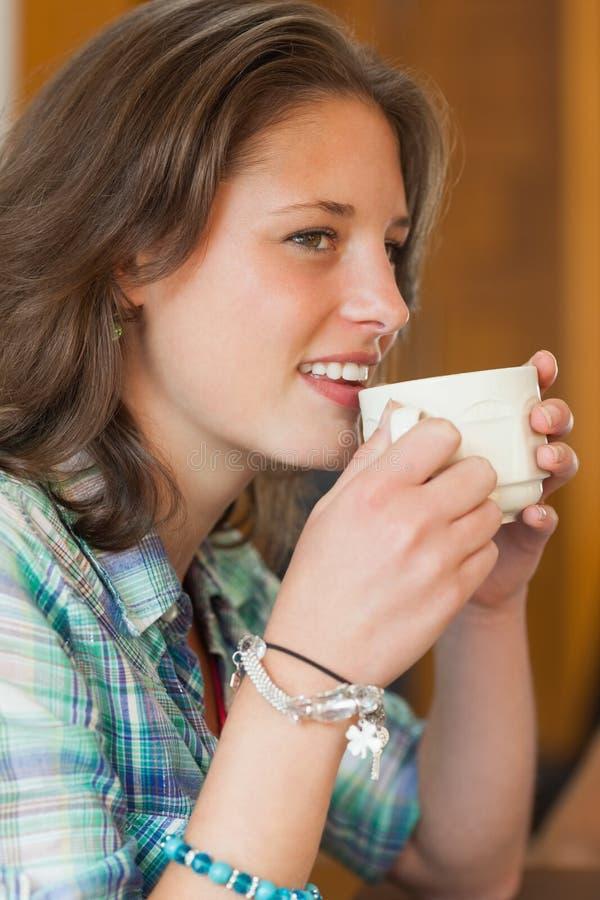 Dosyć rozochocony uczeń pije filiżankę kawy obrazy stock