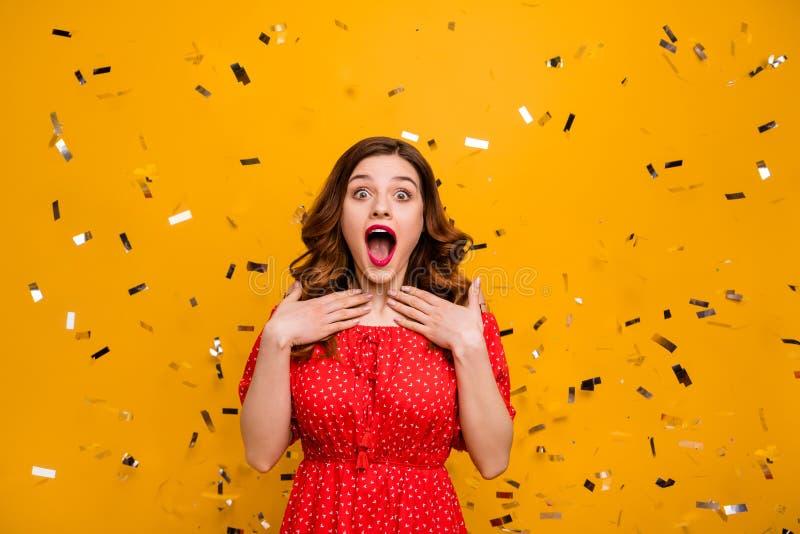 Dosyć skwaśniała dama zaskakująca niespodziewaną przyjęcia urodzinowego ułożenia odzieży czerwieni suknią odizolowywał żółtego tł obrazy stock