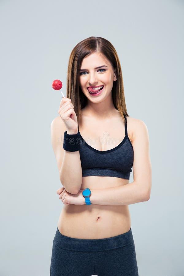 Dosyć sporty kobiety mienia lizak i seansu tonue zdjęcie royalty free