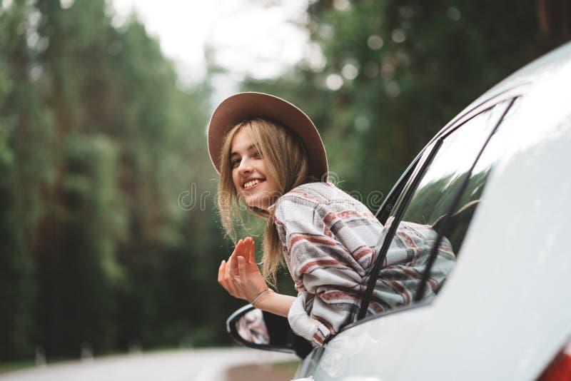 Dosyć, stylowy kobieta podróżnika obsiadanie w samochodowym i patrzeć od okno na dzikiej drodze Boho dziewczyna, podróżomania obrazy royalty free
