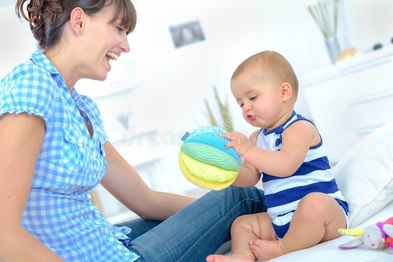 Dosyć szczęśliwa matka bawić się z ślicznym małym berbeciem obraz stock