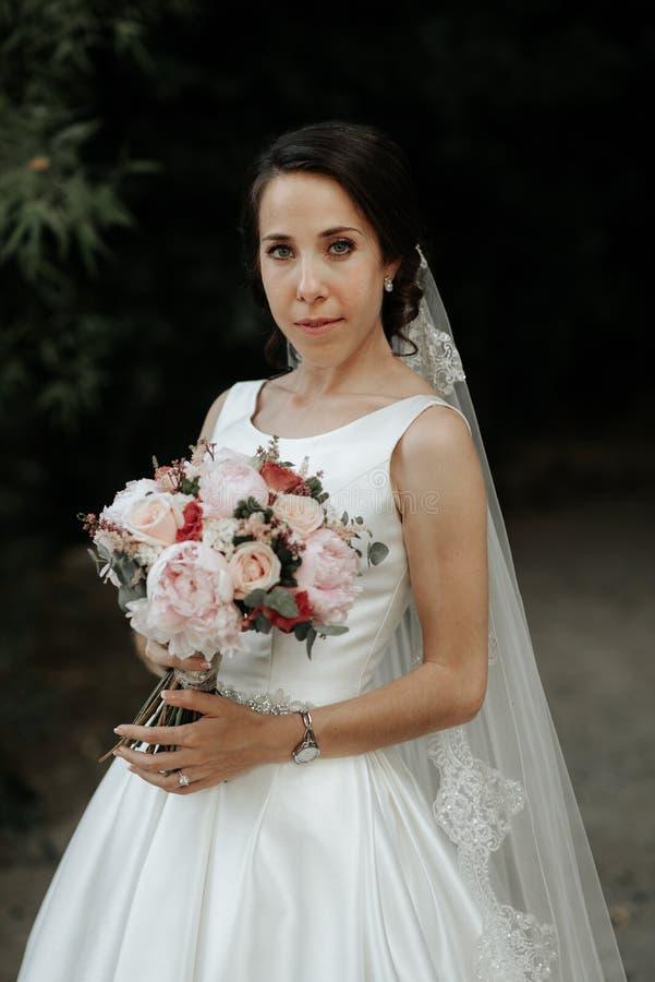 Dosyć szczęśliwa panna młoda w luksus sukni z ślubnym bukietem róże zdjęcie royalty free