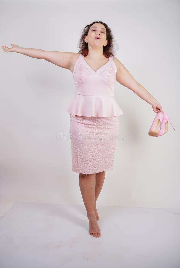 Dosyć tłuściuchna kobieta w menchiach ubiera z patentowej skóry szpilki piętami na białym tle w studiu fotografia royalty free