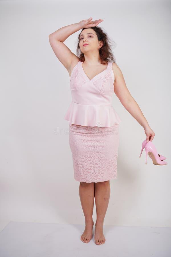 Dosyć tłuściuchna kobieta w menchiach ubiera z patentowej skóry szpilki piętami na białym tle w studiu zdjęcia royalty free