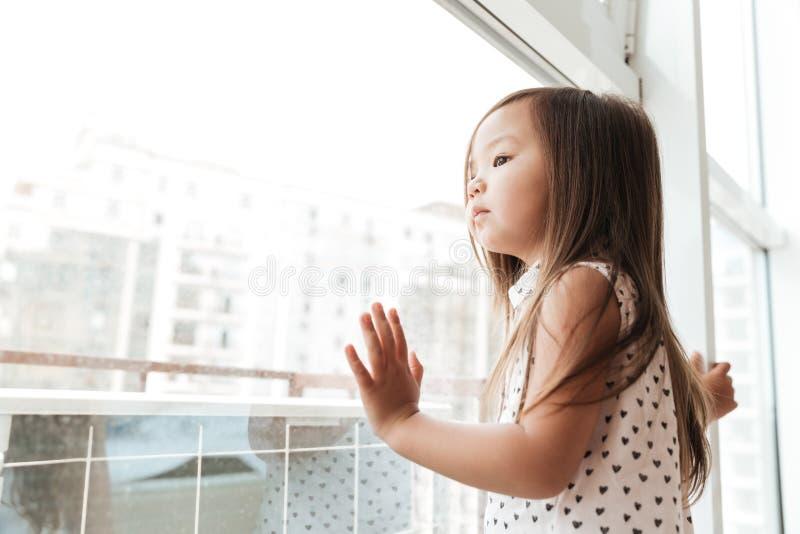 Dosyć trochę śliczna azjatykcia dziewczyna stoi blisko okno w domu zdjęcia stock