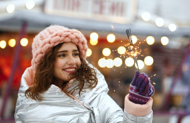 Dosyć uśmiechać się brunetki dziewczyny jest ubranym zima stroju odświętności zimy wakacje przy Bożenarodzeniowym jarmarkiem w Ki zdjęcia stock