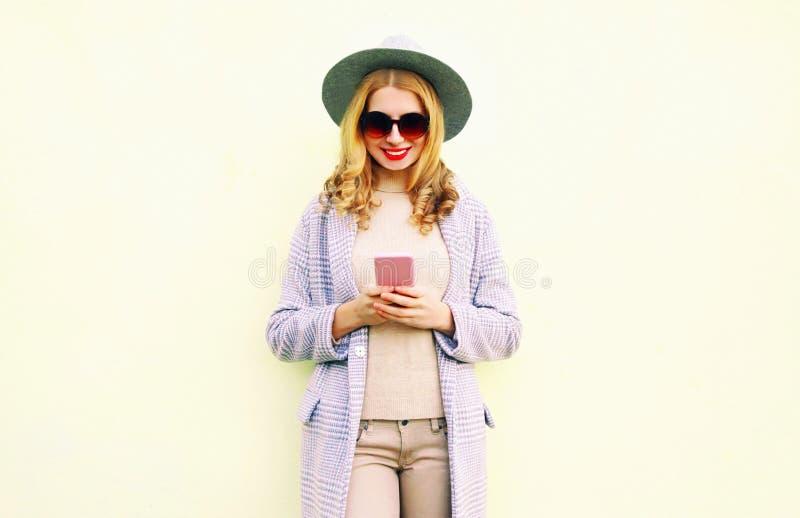 Dosyć uśmiechać się kobiety używa telefon z kędzierzawym włosy w round kapeluszu, żakiet kurtka zdjęcie royalty free