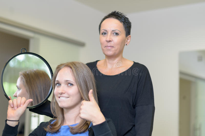 Dosyć uśmiechać się 20s kobiety przy fryzjerami obraz stock