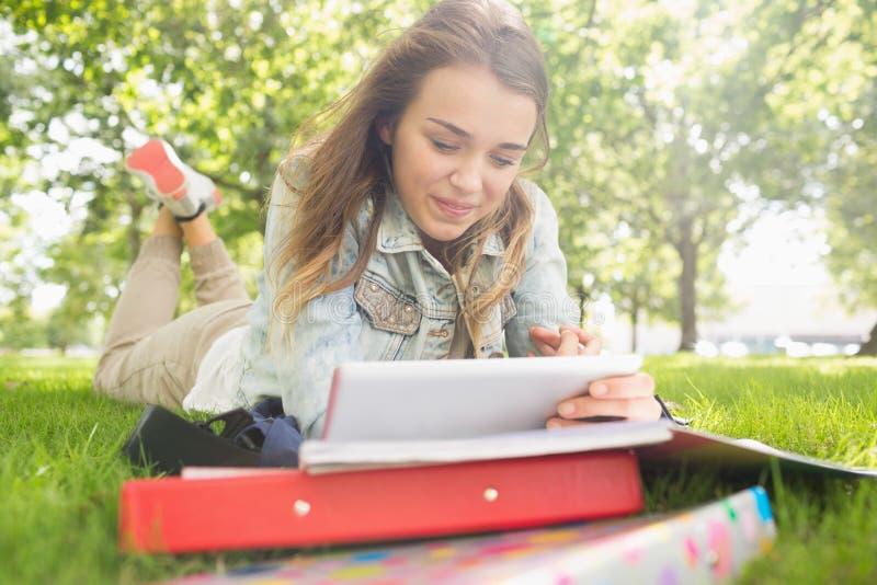 Dosyć uśmiechać się studenckiego lying on the beach na trawy studiowaniu z jej pastylka komputerem osobistym fotografia stock