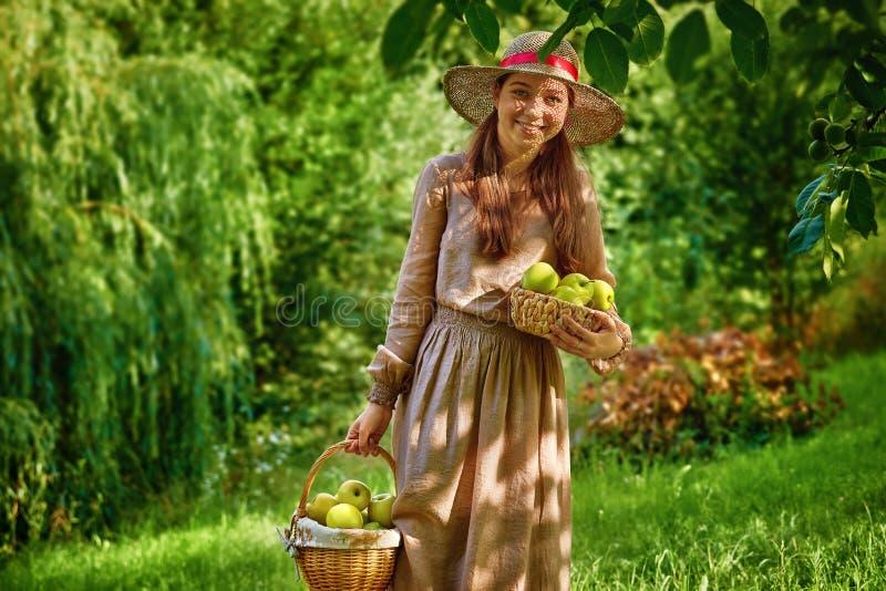 Dosyć uśmiechający się nastolatek dziewczyny w ogródzie z jabłkami koszykowymi obrazy stock