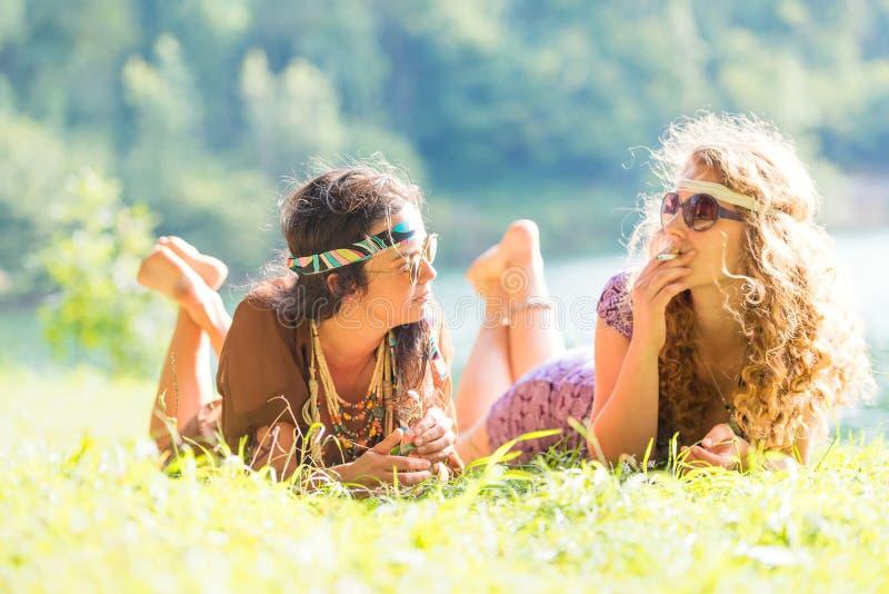 Dosyć uwalnia hipis dziewczyny kłaść na trawie - rocznika skutek ph zdjęcie royalty free