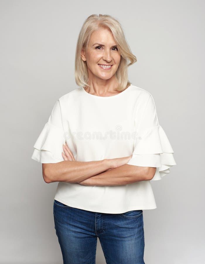 Dosyć w średnim wieku blondynki kobieta jest uśmiechnięta i patrzejąca kamerę odosobniony fotografia royalty free
