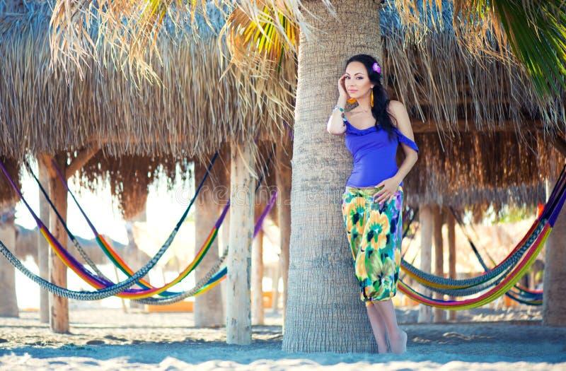 Dosyć zdziwiona rozochocona młoda dziewczyna ono uśmiecha się wewnątrz na tle palmy i hamaki na plaży, styl życia, garbnikujący zdjęcia stock