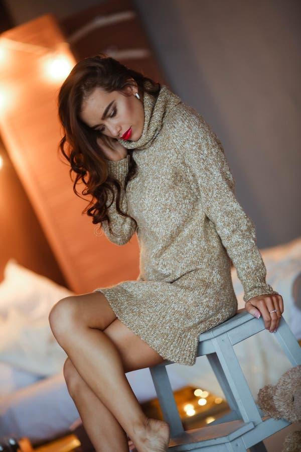 Dosy? elegancka dziewczyna w sukni z fryzury i makeup obsiadaniem przy kanap? Moda splendoru portret fotografia royalty free