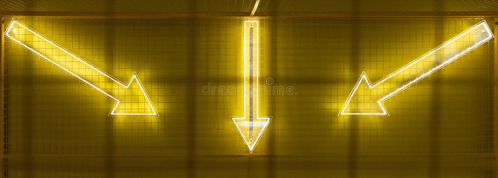 Dots matrix led diplay panel with illuminated symbol of arrow. Background, dark, decoration, pattern, sign, yellow, abstract, design, electric, icon, light royalty free stock photo