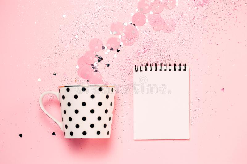 Dotted cup of coffee and note book on pink confetti background royalty free stock photography