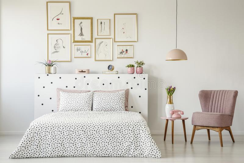 Dotted, double bed, paintings with gold frames and pink armchair royalty free stock photography