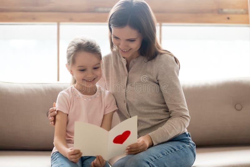 Dotter för lycklig mamma som och för liten unge rymmer läsninghälsningkortet arkivfoto