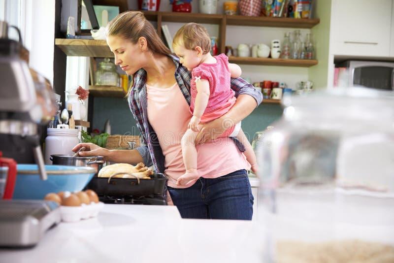 Dotter för stund för modermatlagningmål hållande i kök arkivfoton