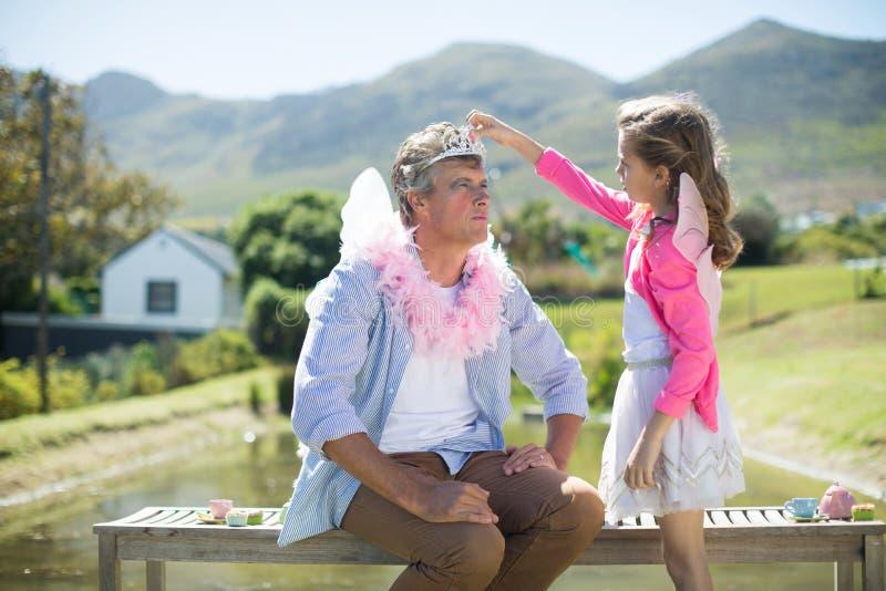 Dotter i ängeldräkt som justerar kronan på faderhuvudet fotografering för bildbyråer