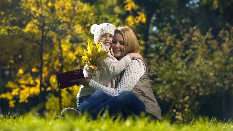 Dotter med höstsidor och kvinnainnehavboken, lyckligt omfamna för familj arkivfoton