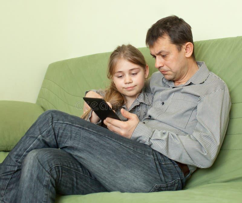 Dotter och fader som använder eBook royaltyfri fotografi