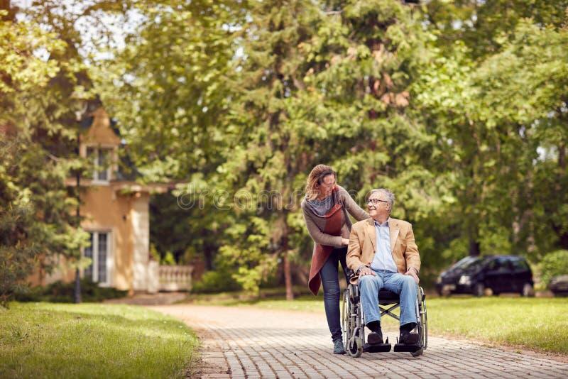 Dotter och hög man i rullstol på att gå den gröna naturen royaltyfri bild