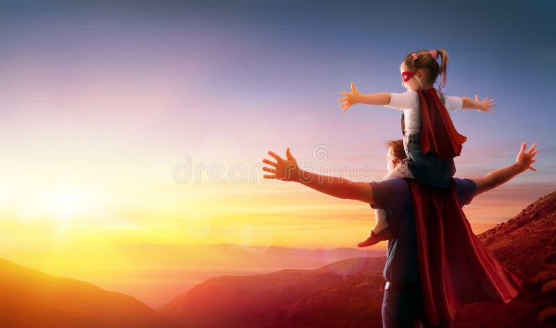 Dotter och hennes fader Dressed As Heroes royaltyfria foton