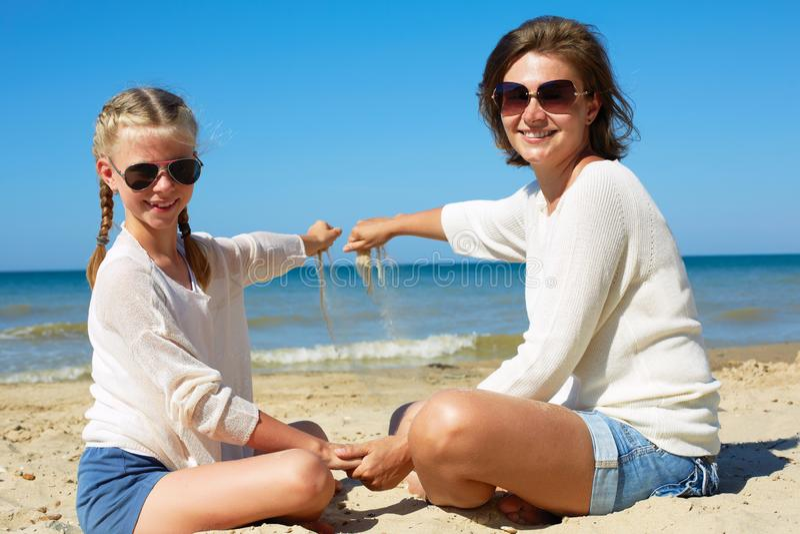 Dotter och hennes mamma som spelar med sand p? stranden royaltyfri bild