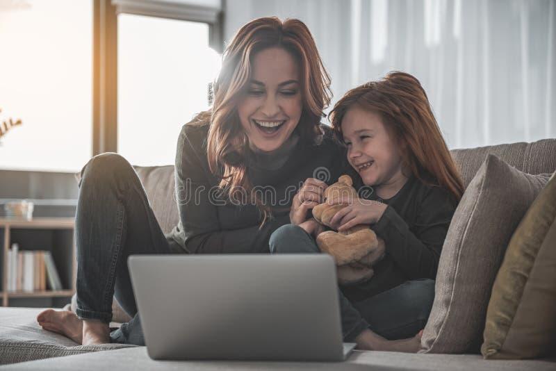 Dotter och moder som skrattar med spänning, medan hålla ögonen på film royaltyfri bild