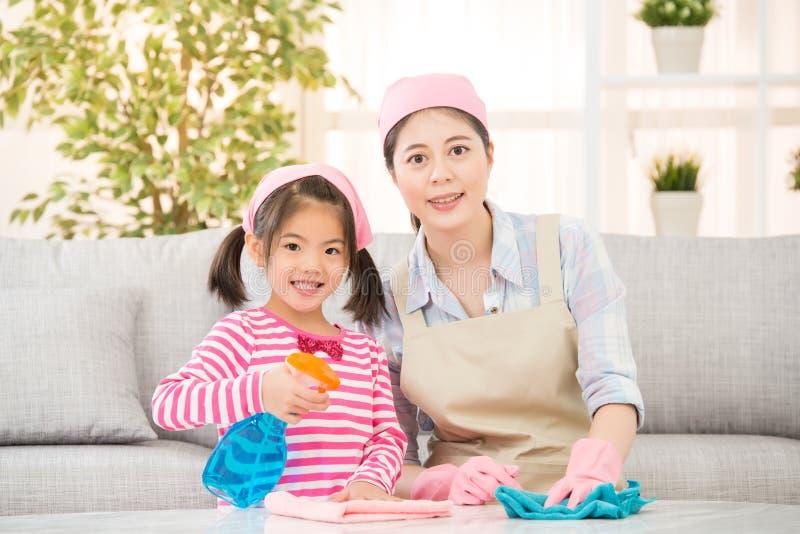 Dotter och moder som tillsammans gör ren royaltyfria bilder