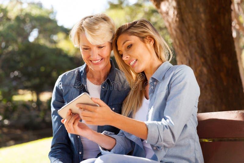Dotter som använder den smarta telefonen royaltyfri fotografi