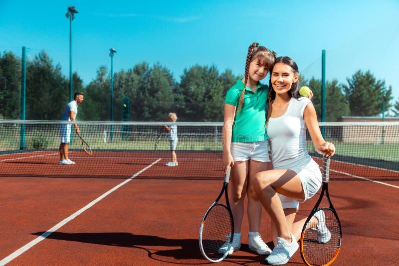 Dotter som bär den gröna t-skjortan som kramar mamman, innan att spela tennis arkivfoto