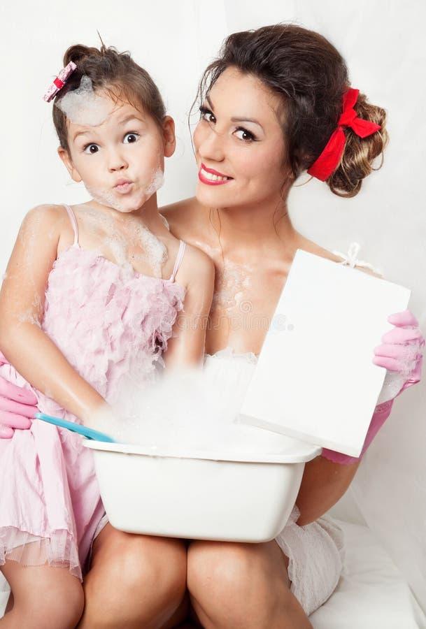 dotter som gör tvätterimodern royaltyfria foton
