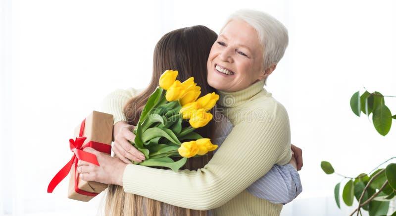 Dotter som ger blommor och gåva till hennes moder arkivfoto