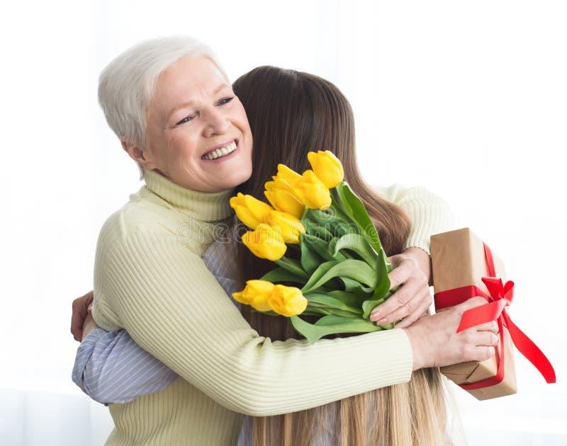 Dotter som ger blommor och g?va till hennes moder royaltyfri foto