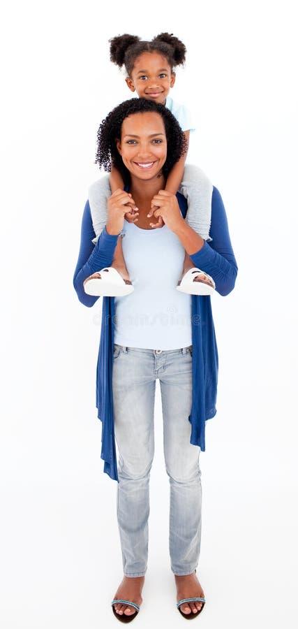 dotter som ger henne att le för moderpiggibackritt royaltyfria bilder