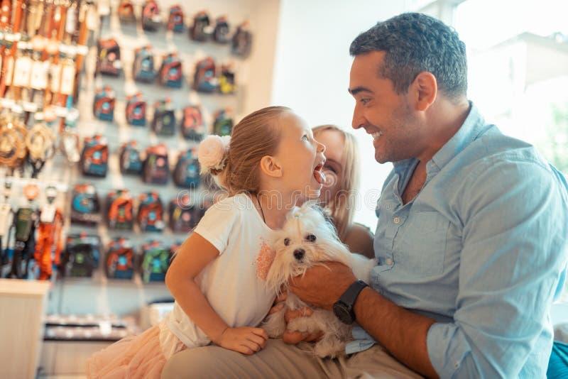 Dotter som har gyckel, medan komma att dalta för att shoppa med föräldrar och hunden arkivbild