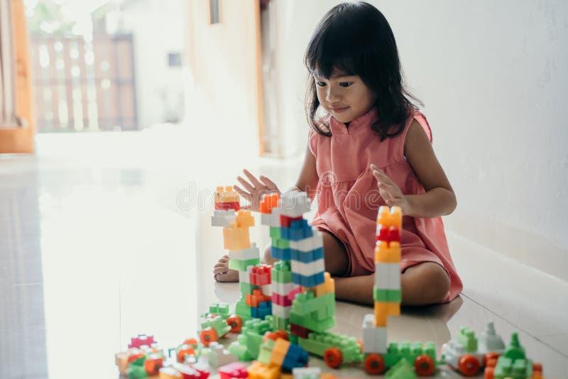 Dotter som hemma spelar med plast- tegelsten royaltyfria bilder