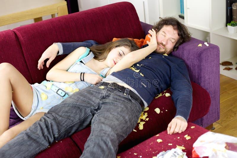 Dotter som kramar fadern på soffan som sover med kaos omkring arkivfoto