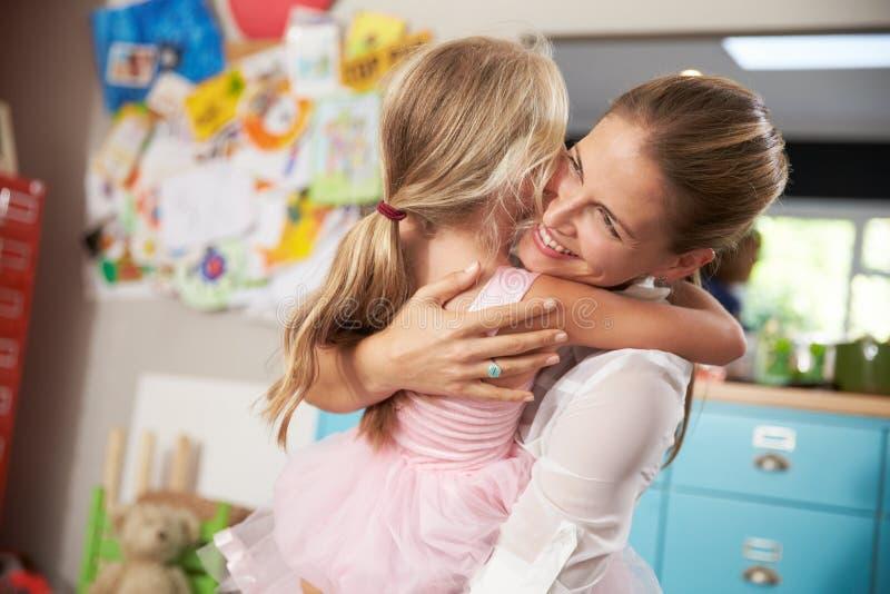 Dotter som kramar modern som går tillbaka från arbete royaltyfri foto