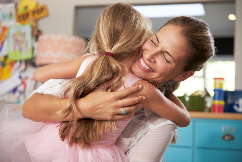 Dotter som kramar modern som går tillbaka från arbete royaltyfria foton