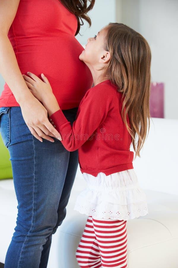 Dotter som lyssnar till gravida moders mage arkivfoto