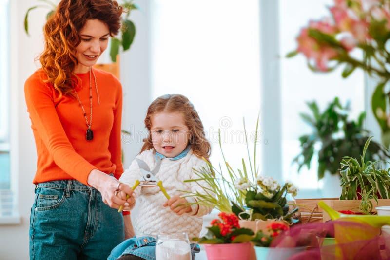 Dotter som rymmer plattång, medan ta omsorg av växter med mamman arkivfoton