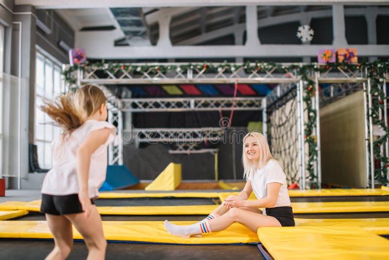 Dotter som studsar på trampolinen medan moderklocka för säkerhet royaltyfri bild